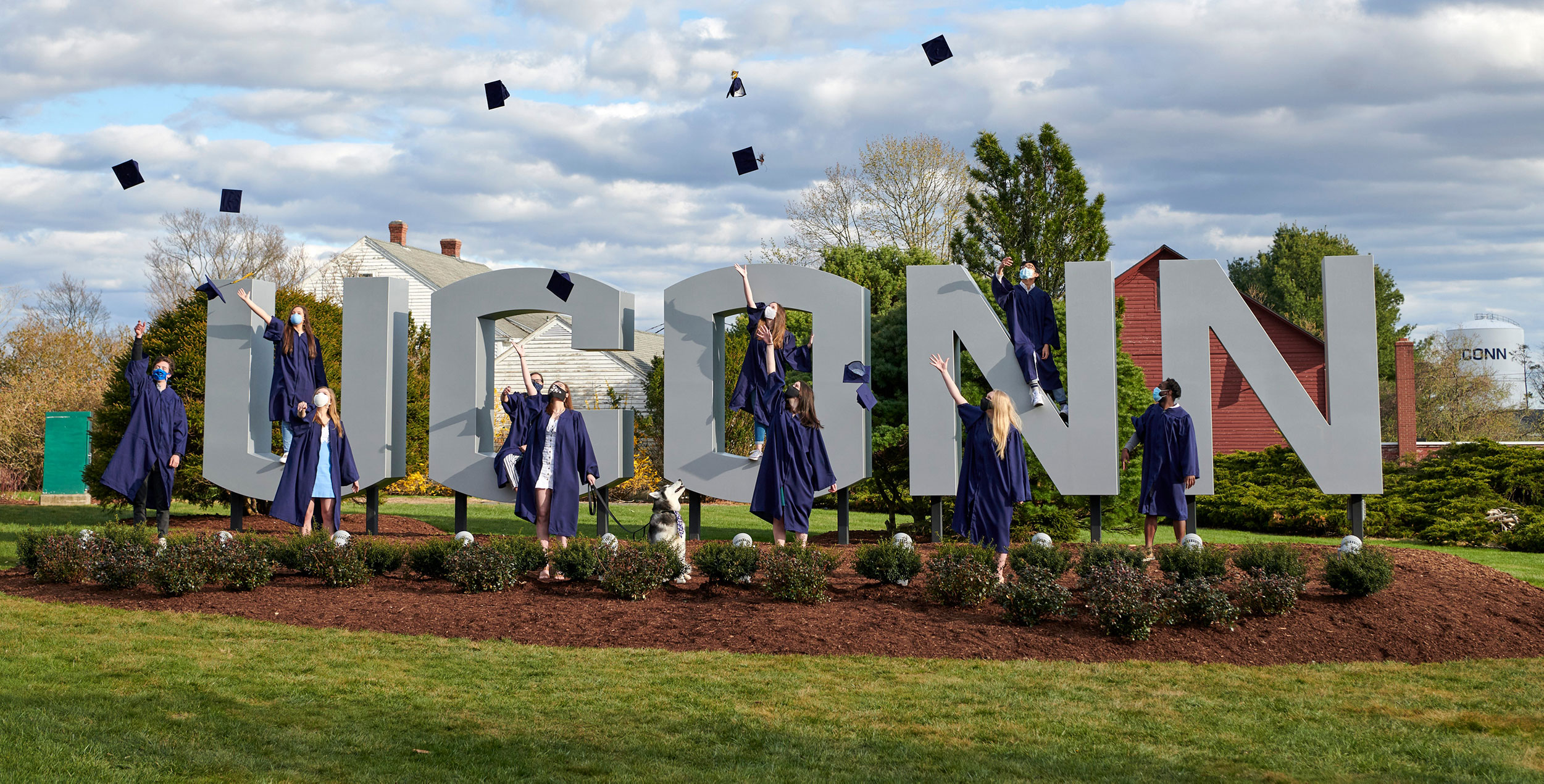 Students in commencement regalia throw their caps joyfully in front of the UConn Storrs gateway sign